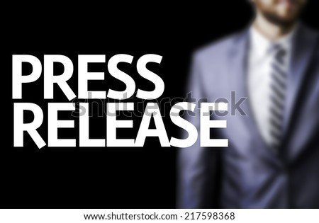 Press Release written on a board with a business man on background - stock photo