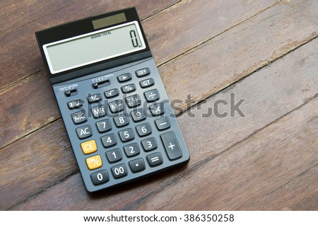 Press the button on the calculator with a wooden floor in the background. - stock photo