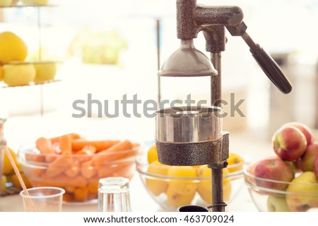 Press the preparation of fresh juices on a background of fresh fruits and vegetables.