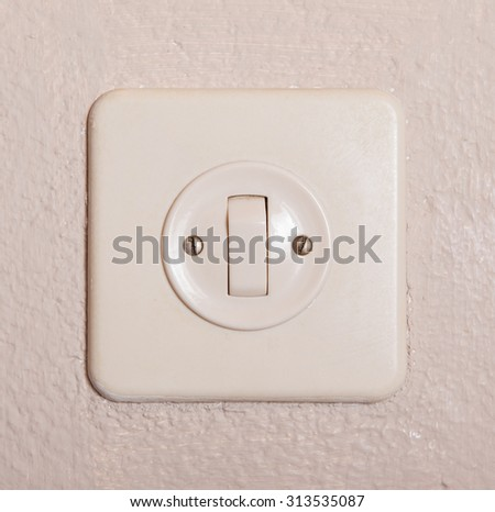 Press turn on/off electrical switch, old plaster wall