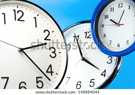 Pressed for time. Three wall clocks on blue background.
