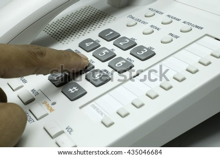 Pressing a number on telephone. - stock photo