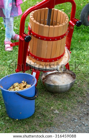 Pressing of fresh apple juice in a traditional method - stock photo