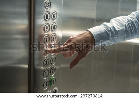Pressing the button in the elevator - stock photo