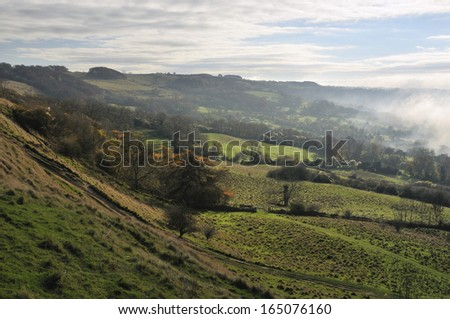 Prestbury Hill viewed from Cleeve Common Fort with Fog in the Valley - stock photo