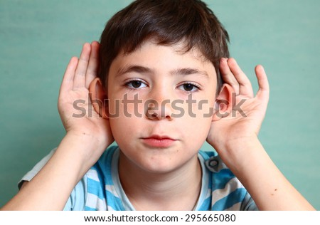preteen beautiful boy hold his hear isolated on blue - stock photo