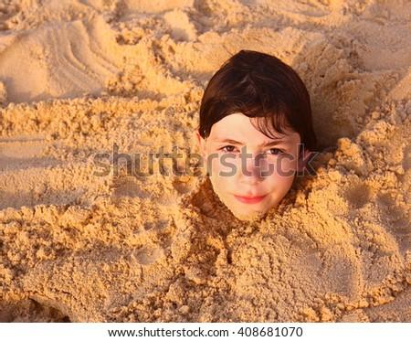 preteen boy head in the beach sand happy smiling - stock photo