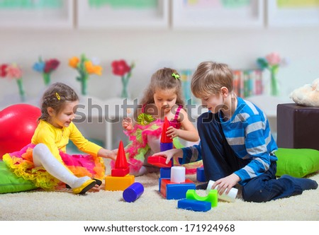 Preteen boy playing with two younger girls - stock photo