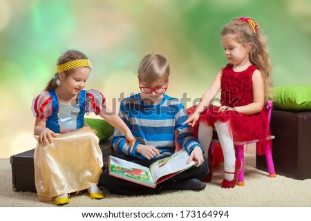 Preteen boy reading a fairy tale to two little girls and showing them the book pictures