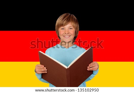 Preteen boy with a big book and the colors of German flag of background - stock photo