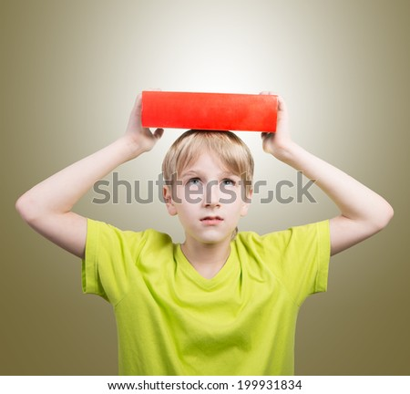 Preteen boy with a book on his head - stock photo