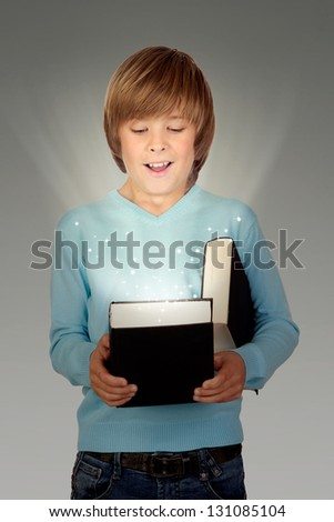 Preteen boy with a lighted book isolated on gray background - stock photo