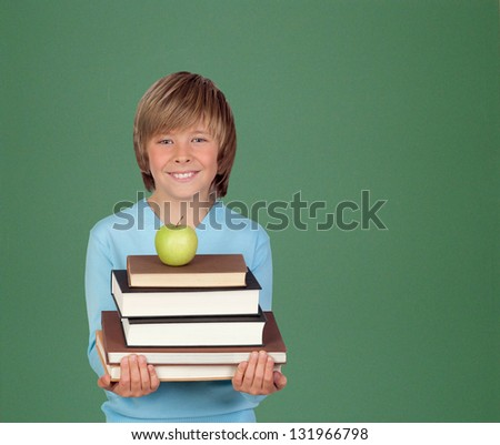Preteen boy with a many books with a green blackboard for background - stock photo