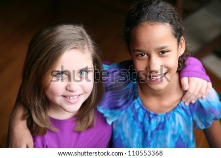 preteen caucasian and african-american girls smiling - stock photo