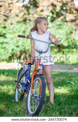 Preteen Caucasian girl standing in summer park with cycle - stock photo