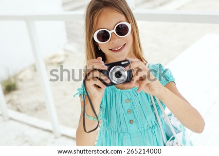 Preteen child resting and taking photos at the beach in summer - stock photo