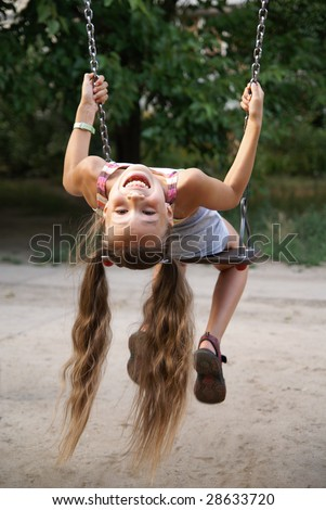Preteen girl having fun on a swing on playground - stock photo