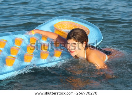preteen girl in swimming suit with inflatable matress on the blue sea  - stock photo