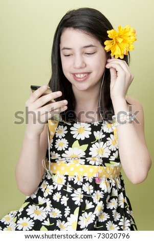 Preteen girl listening to mp3 player with earbuds - stock photo