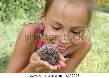 Preteen girl on meadow with porky-pine - stock photo