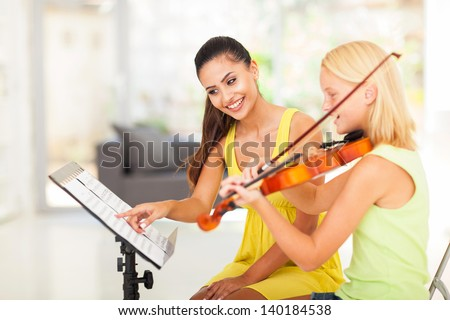 preteen girl play violin under music teacher's instructions - stock photo