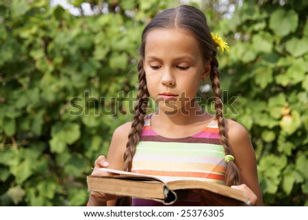 Preteen girl reading book on green leaf background