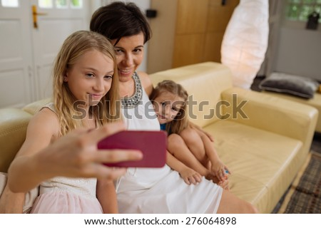 Preteen girl taking selfie with her mother and little sister