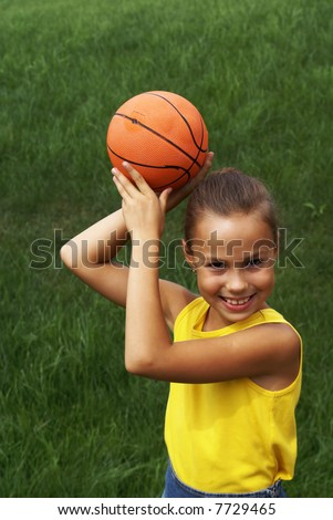 Preteen girl with basketball on grass background - stock photo