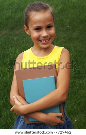 Preteen girl with books on grass background