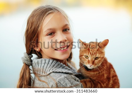 Preteen girl with red cat in her arms.  - stock photo