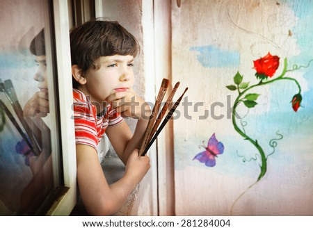 preteen handsome artist boy with brushes and his painting on the background wall - stock photo