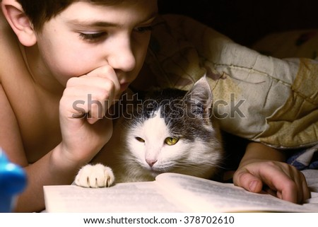 preteen handsome boy evening read book with cat in the bed before sleep - stock photo