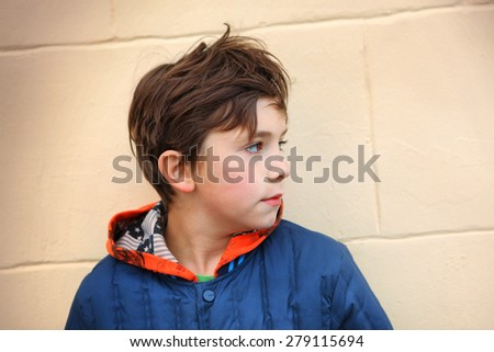 preteen handsome boy half face close up portrait on the beige wall background - stock photo