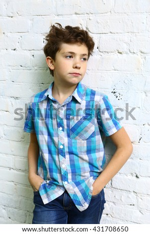 preteen handsome boy in checked blue shirt close up portrait on white brick wall background - stock photo