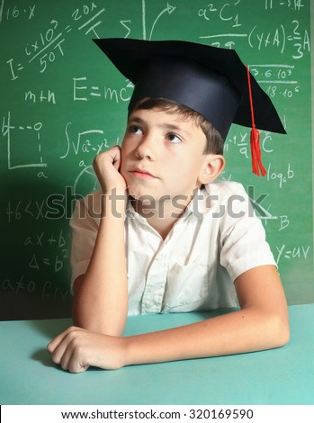preteen handsome boy in graduation cap on the blackboard background close up portrait