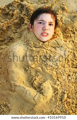 preteen handsome boy in sand with bodybuilder arm made of sand close up portrait - stock photo