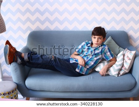 preteen handsome boy lay on the sofa  - stock photo