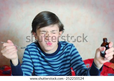 preteen handsome boy make a grimace after taking bitter medicine - stock photo