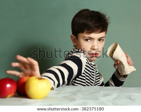 preteen handsome boy make choice between healthy food apples and fast food caesar roll - stock photo