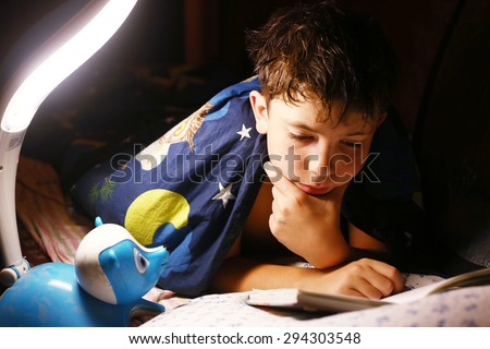 preteen handsome boy read book with lamp before sleep - stock photo