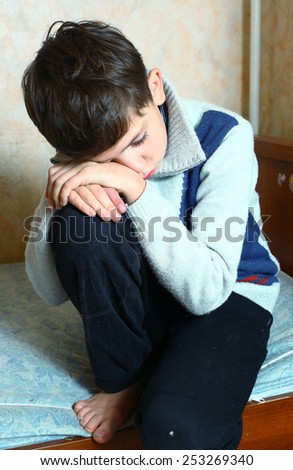 preteen handsome boy sit on the bed sad and depressed - stock photo