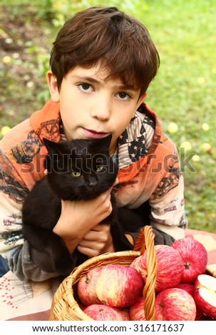 preteen handsome boy with black cat and red apples close up portrait