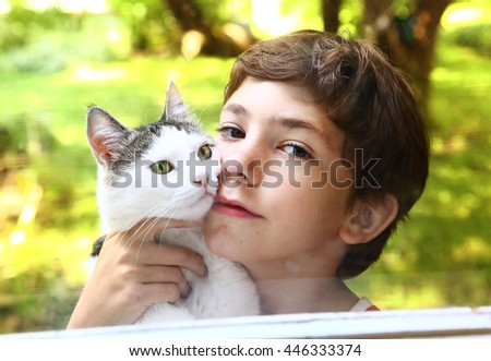 preteen handsome boy with cat close up photo through the window on the summer garden background - stock photo