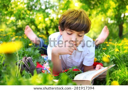 preteen handsome keen boy red and old book in the summer park with dandelion flowers - stock photo