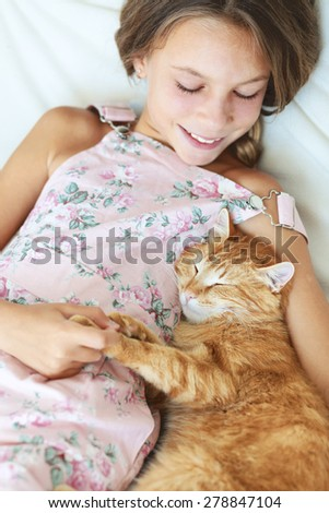 Preteen school girl of 8-9 years old with her pet resting on a sofa at home - stock photo