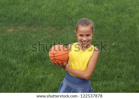 Preteen school girl with basketball on green grass background outdoors