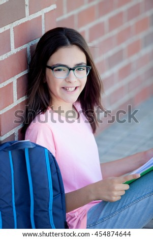 Preteenager girl next to a red brick wall with the backpack sitting on the floor - stock photo