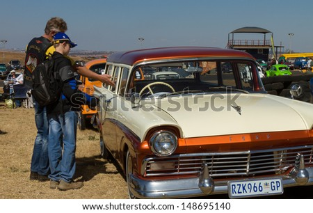 PRETORIA, SOUTH AFRICA - AUGUST 4:  An unknown man and boy admiring a 1957 Ford station wagon at Cars in the Park - South Africa's biggest vintage car show - on August 4, 2013 in Pretoria. - stock photo