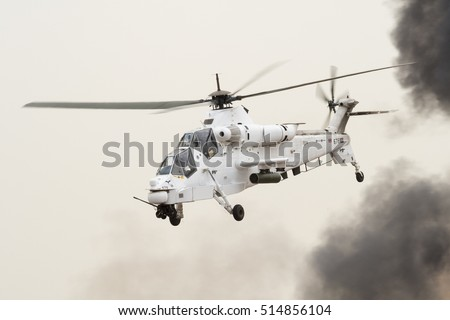 PRETORIA, SOUTH AFRICA-SEPTEMBER 17 2016: A Rooivalk combat helicopter in white UN colors in front of a black smoke cloud hovering at the African Air Defense show at AFB Waterkloof