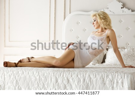 Pretty adult blonde woman wearing white dress laying on bed at a hotel room.